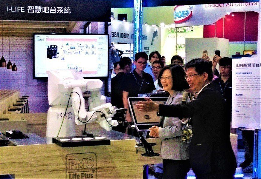 小英總統29日出席台灣機器人與智慧自動化展,向智慧酒保點了一杯可樂。(photo...
