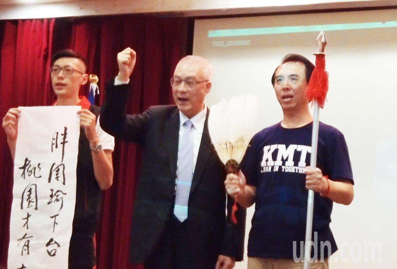 國民黨主席吳敦義(中)贈送桃園市長候選人陳學聖(右)一把長槍和一面羽扇,示意打倒...