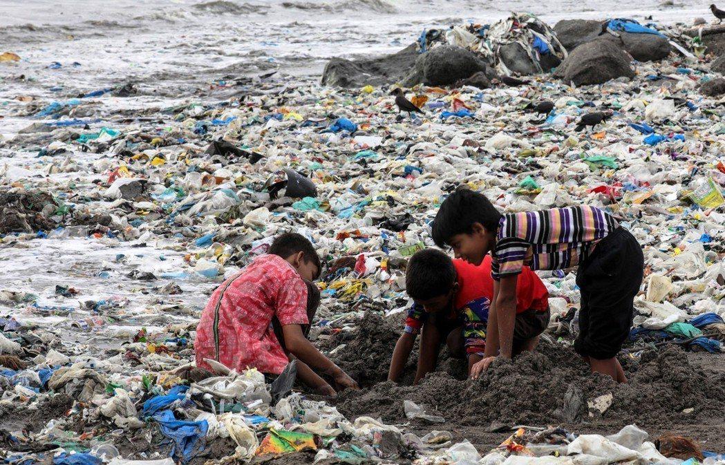 印度孟買的兒童在海岸的垃圾堆中玩耍。圖/歐新社