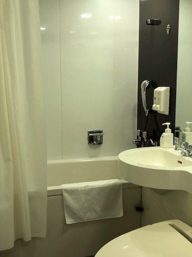 房門右側是個迷你的浴室,看起來是一體成型的組合式衛浴設備。曾經好幾年在遊輪工作的...