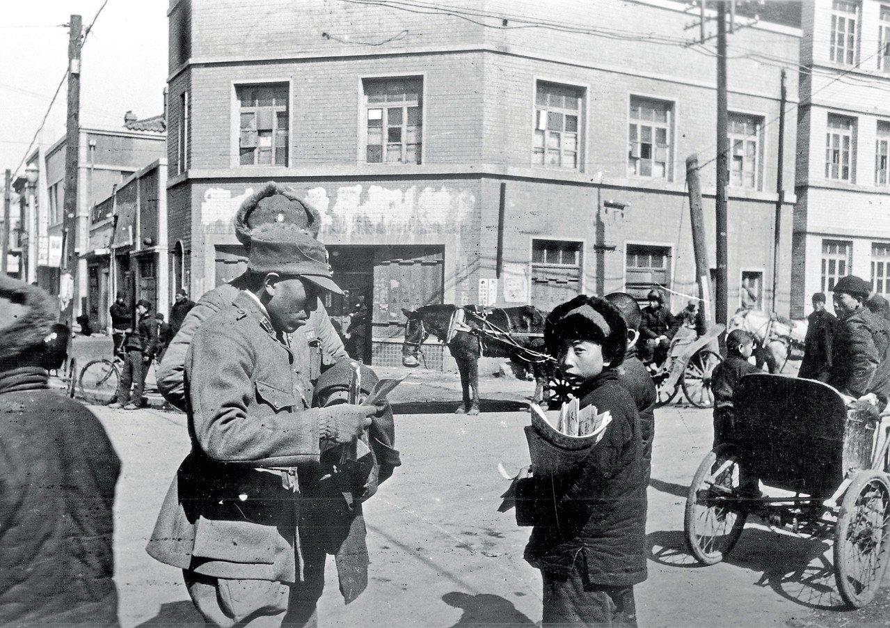 1946年3月,遼寧錦州的一名國軍向街邊的日 本小孩購買報紙。 視覺中國