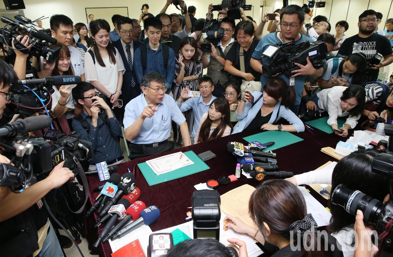 柯文哲上午赴台北市選委會,登記參選連任台北市長,被媒體團團包圍,他索性算一下有幾...