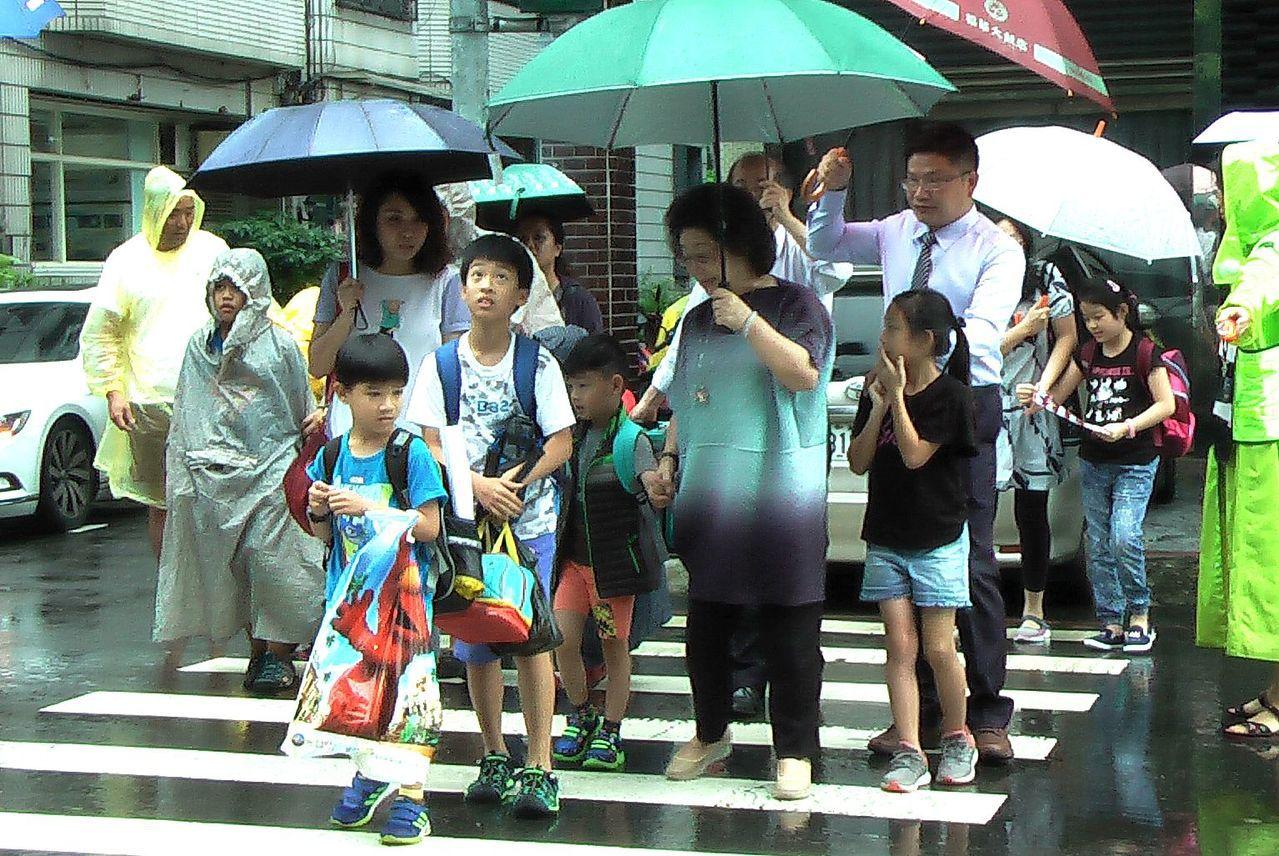 高雄市教育局長范巽綠(中)撐傘護小朋友過馬路。記者徐如宜/攝影