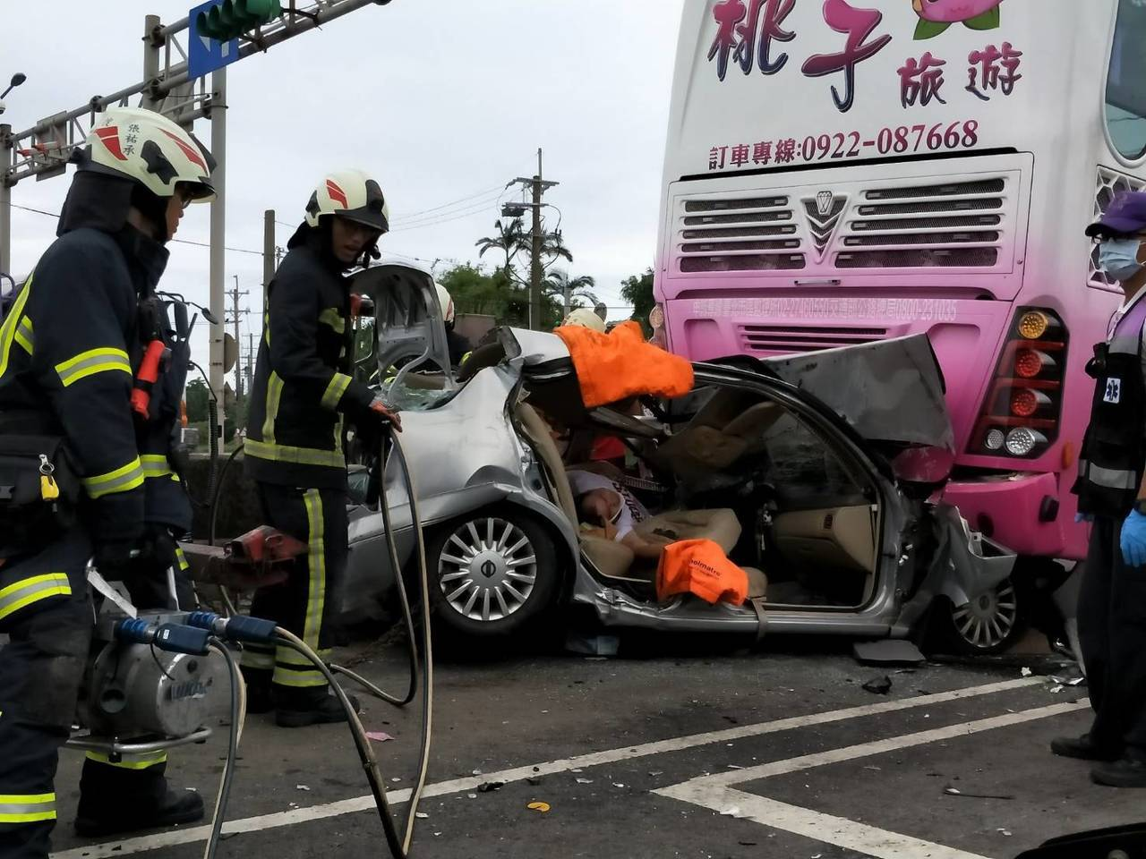 轎車嚴重變形,消防隊員設法救出駕駛座受困男子。記者鄭國樑/翻攝