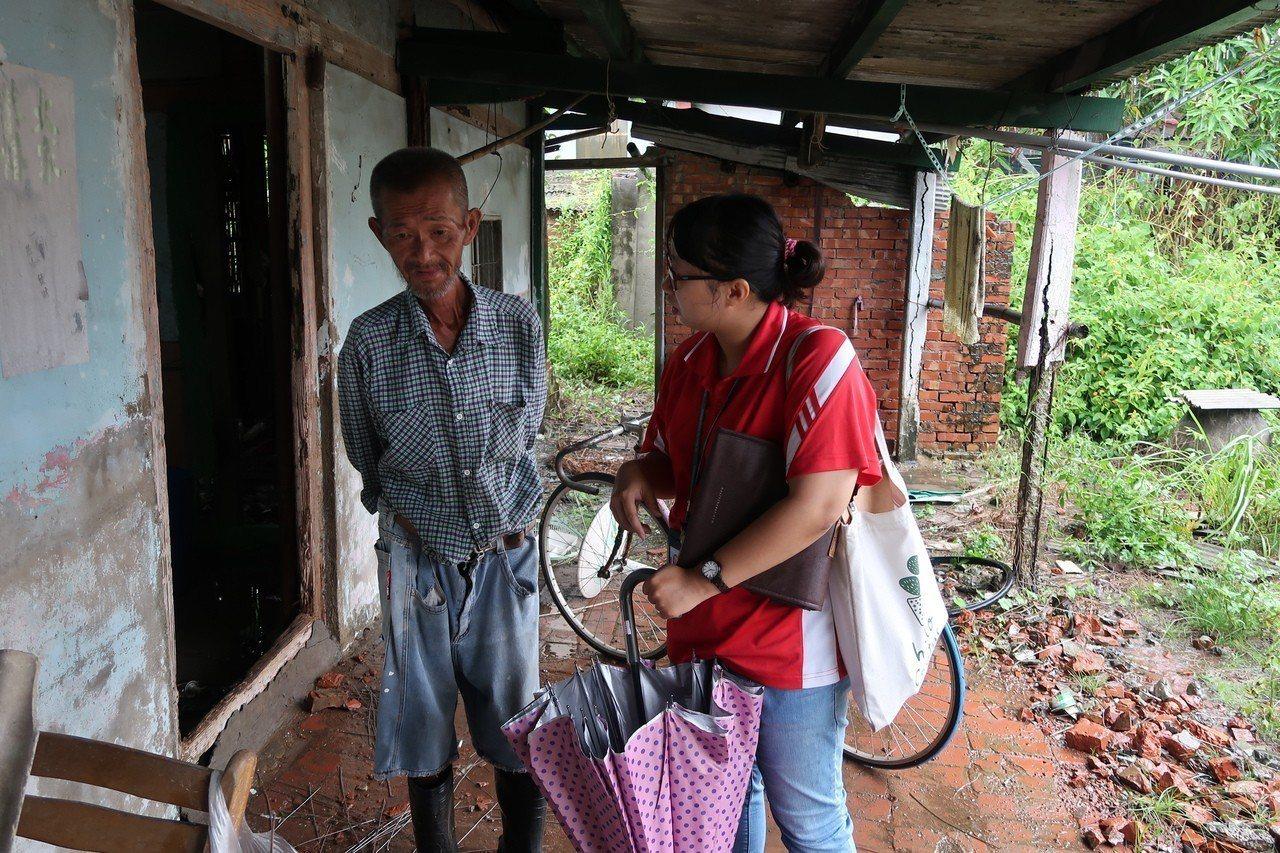 天主教中華聖母基金會社工來到災情最嚴重的東石鄉,探訪未婚獨居的蔡姓阿伯(左)。圖...