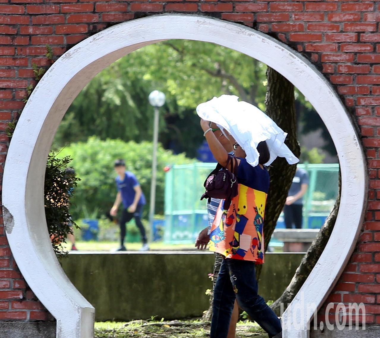 西南氣流減弱,陽光露臉氣溫回升,民眾披著薄外套防曬。記者侯永全/攝影