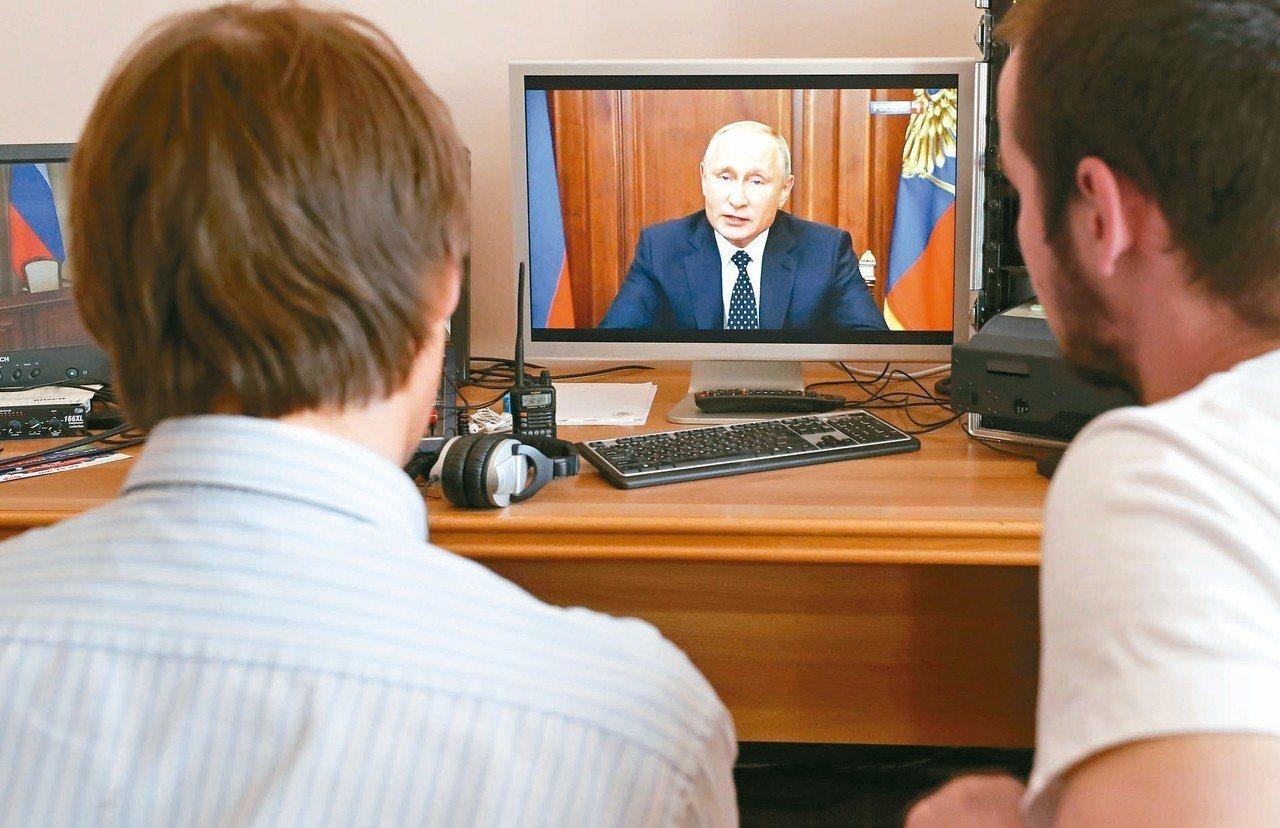 俄羅斯國總統普亭針對年金改革上電視發表演說,民眾聚精會神收看。(歐新社)