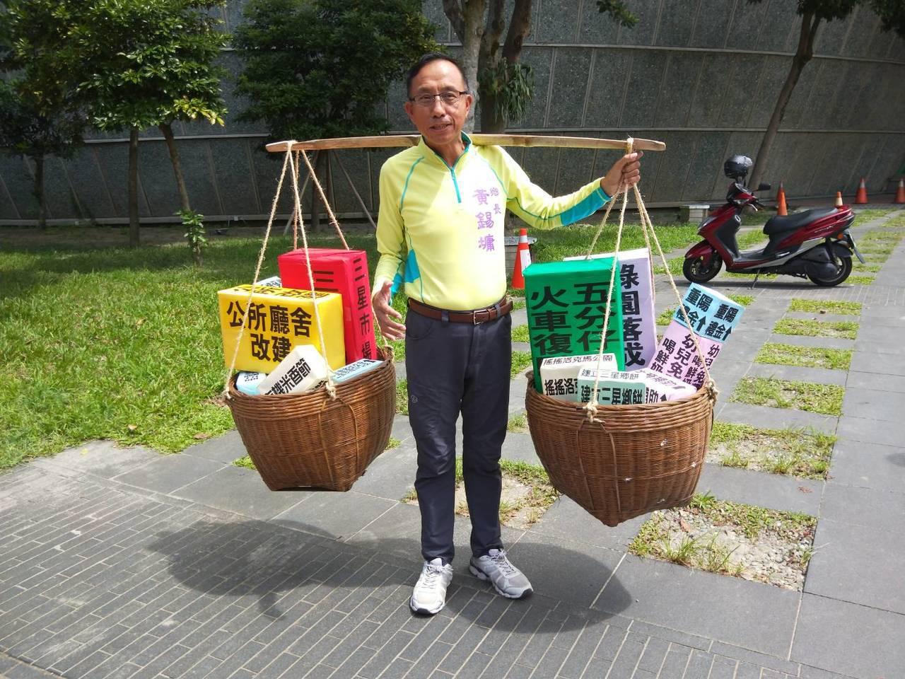 宜蘭縣議員參選人黃錫墉將六年來的政績用扁擔一肩扛起,象徵承擔起三星鄉的未來。記者...