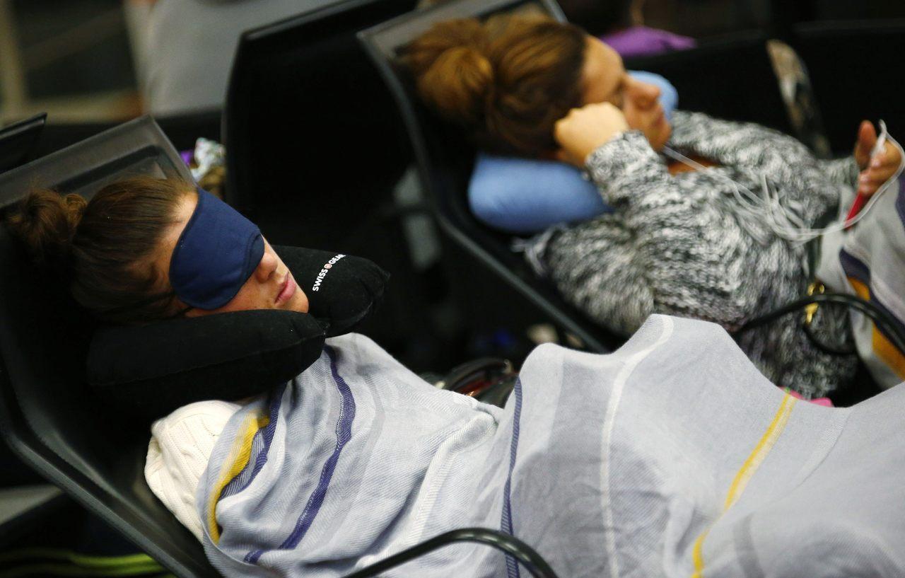 許多乘客將搭機時間用來補眠,但也有人在飛機上遇見靈魂伴侶,此為示意照。路透