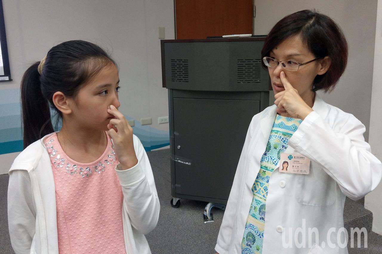 醫師陳亮如(右)教導許姓女童(左)鼻呼吸方式,即閉上嘴巴後,按住單側鼻孔,吸飽氣...