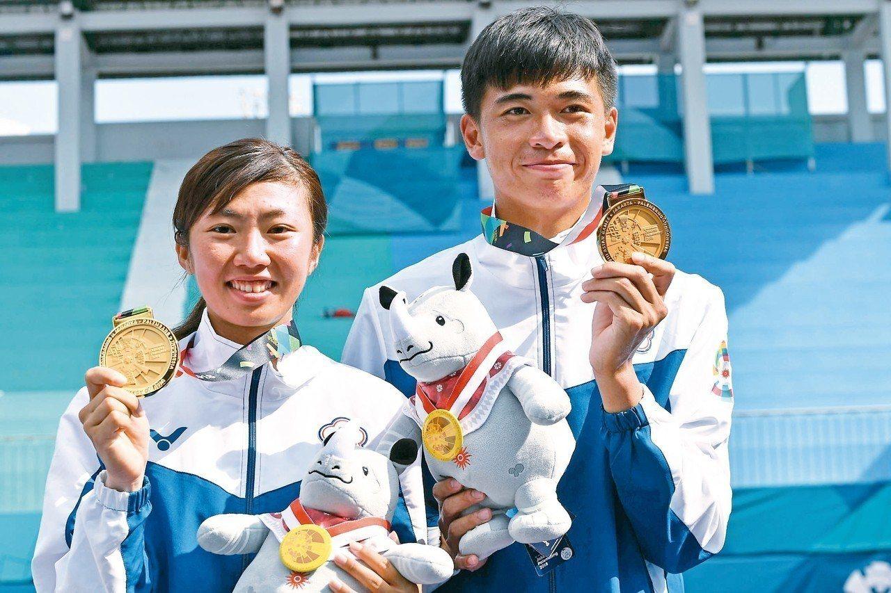 我國余凱文(右)與鄭竹玲在亞運軟網混雙摘金,持著金牌露出笑容。 (法新社)