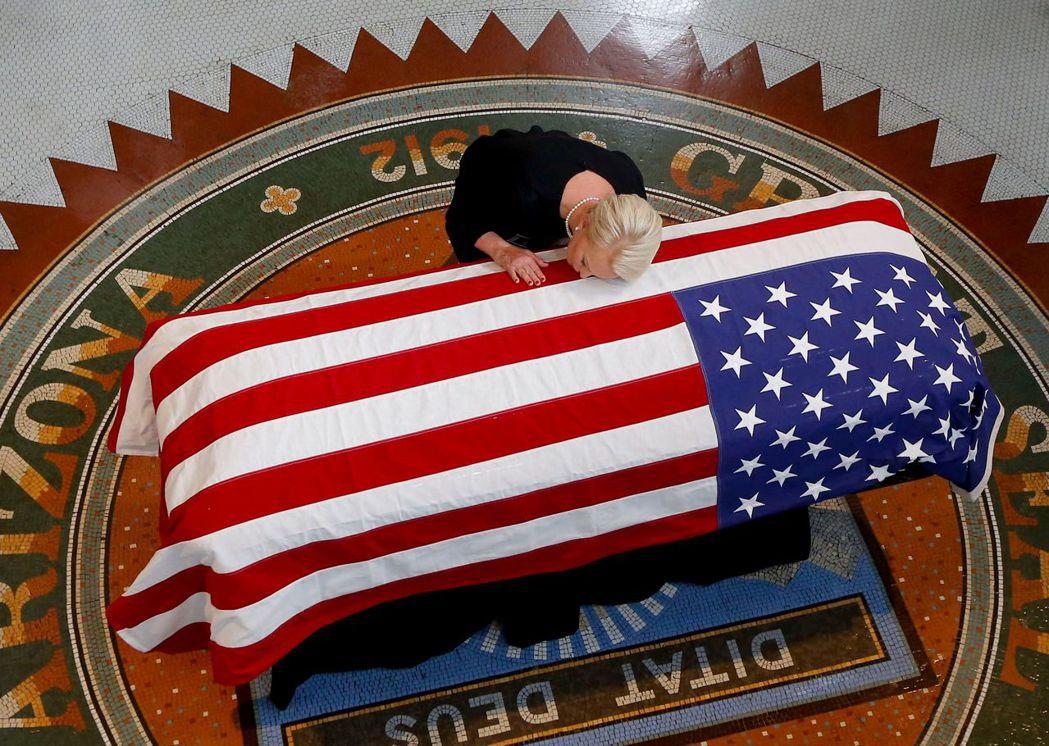 在亞歷桑納州議會大廈內,馬侃遺孀辛蒂29日親吻馬侃靈柩。 (法新社)