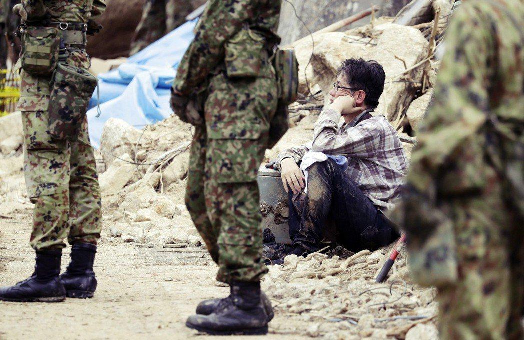 7月11號水災後結束後,一名真備町的災民正蹲坐在路旁,他的家人則下落不明。 圖/...