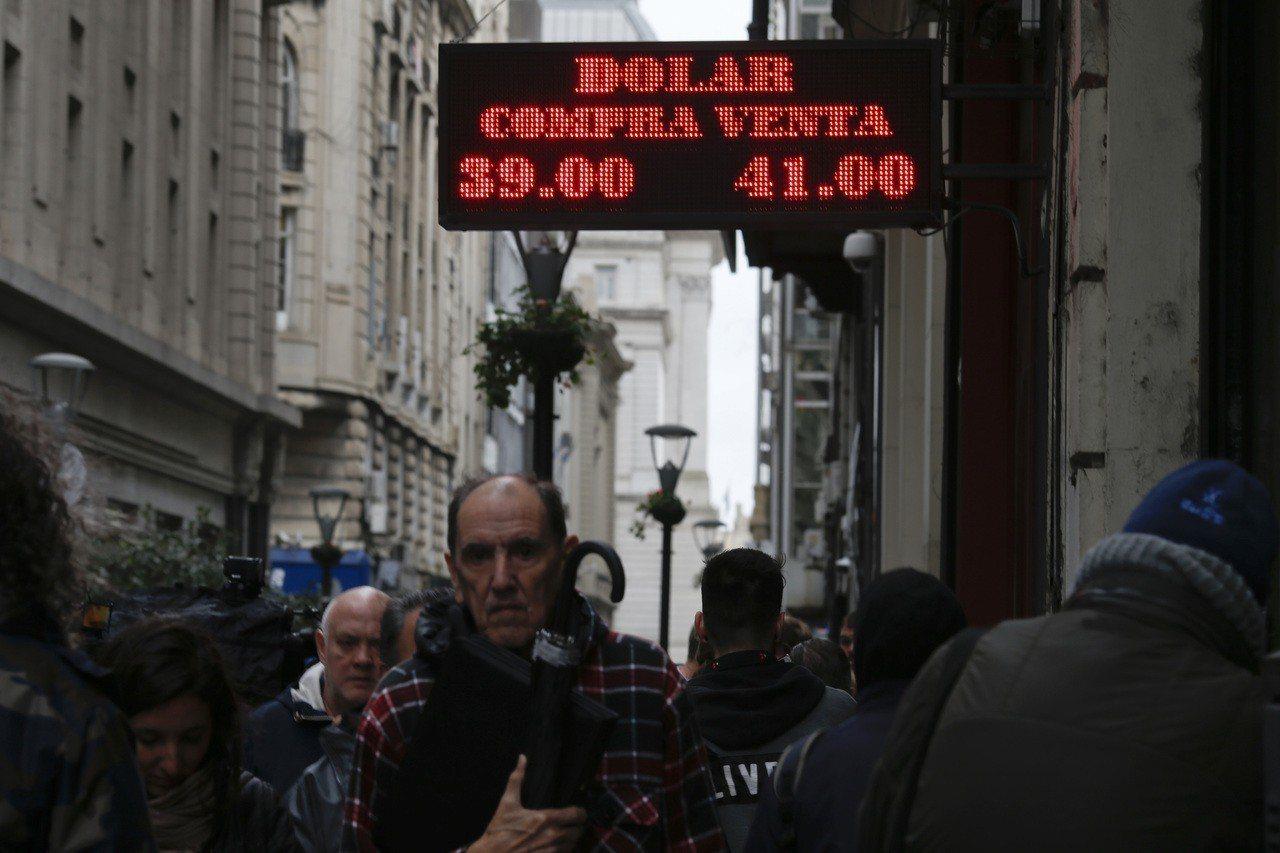 阿根廷民眾30日經過首都布宜諾斯艾利斯的貨幣兌換店。阿根廷央行30日閃電升息,將...