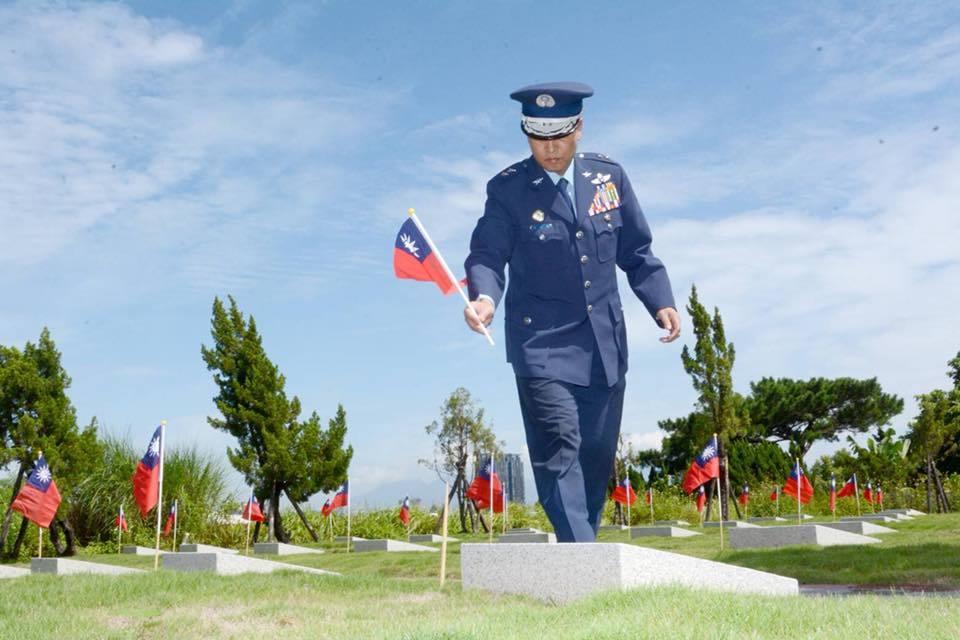 空軍司令張延廷,在碧潭公墓的烈士墳前插上國旗。圖/引自空軍臉書網頁