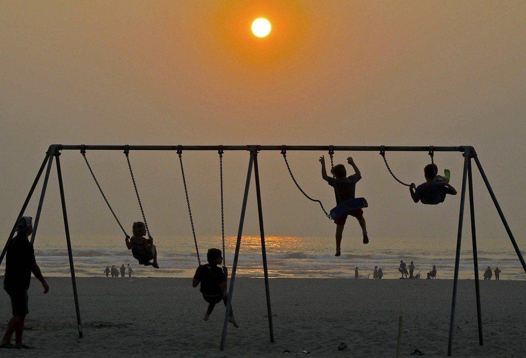 幾個孩子在俄勒岡州太平洋沿岸沙灘上盪鞦韆,霧霾讓夕陽和天空一片灰濛。 (美聯社)