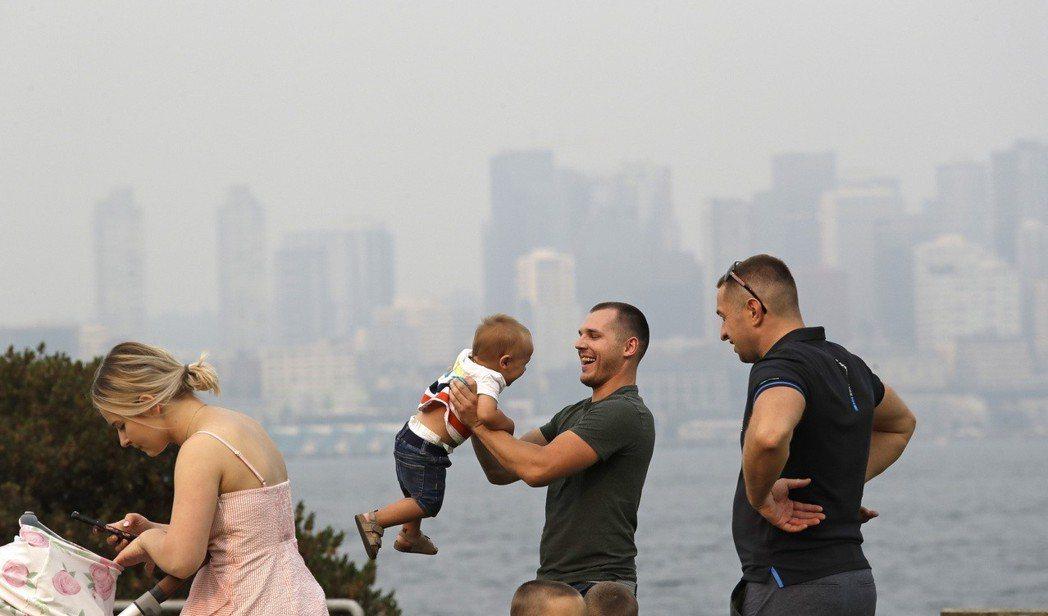 一群遊客在西雅圖親水公園遊玩,遠方的市中心籠罩在霧霾中。 (美聯社)