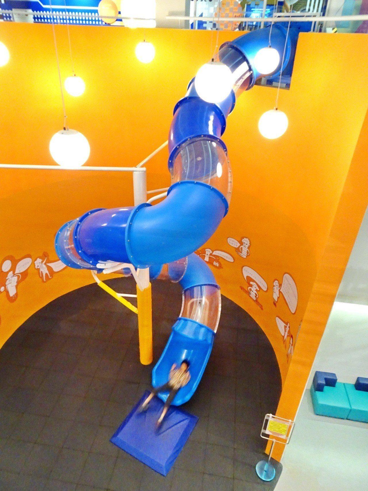 台電南部展示館新設2樓高、象徵核能反應爐的「電力」溜滑梯,橘色弧形牆代表反應爐水...