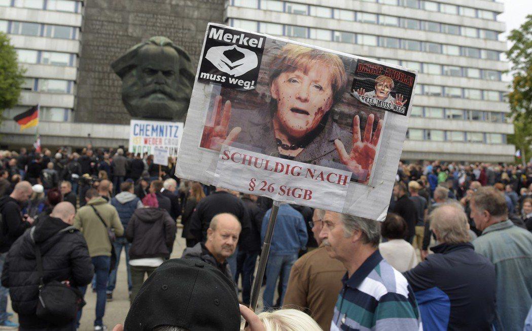 一名示威者舉著寫著「梅克爾必須下台」的海報,參與德國肯尼茨市的反移民示威。 (美...