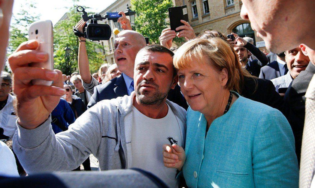德國總理梅克爾(右)2015年在柏林一處收容中心和難民自拍。 (路透)