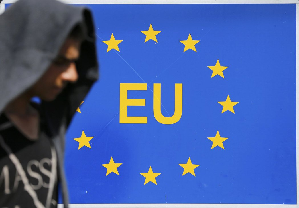 一名難民2015年在塞爾維亞境內走過歐盟的標誌。 (路透)