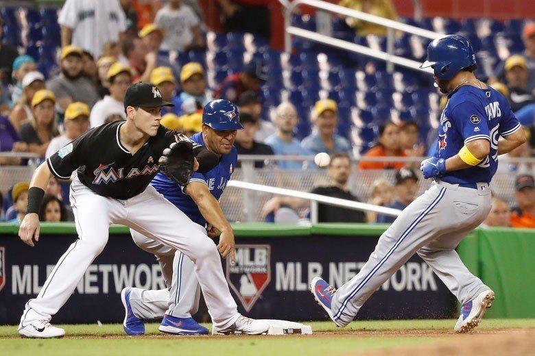 藍鳥隊崔維斯(右)藉隊友史莫克的右外野高飛犧牲打推進到三壘,接下葛里奇克又打出左...