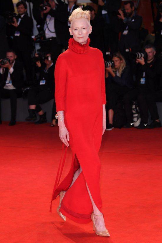 蒂妲史雲頓選穿Haider Ackerman的紅色禮服,抓皺高領設計搭配她一貫俐...