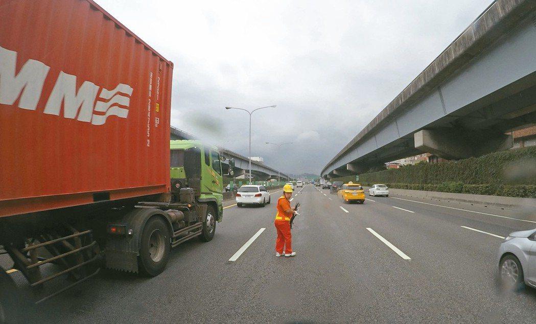 車輛爆胎產生的胎皮高居國道散落物第一,國道事故班成員冒險在呼嘯車流中迅速清理撿拾...