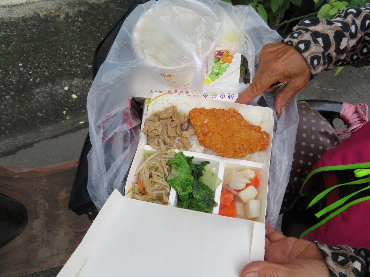 水上鄉志工張財福騎機車餐獨老,便當有炸豬排等4菜及米飯。 記者魯永明/攝影