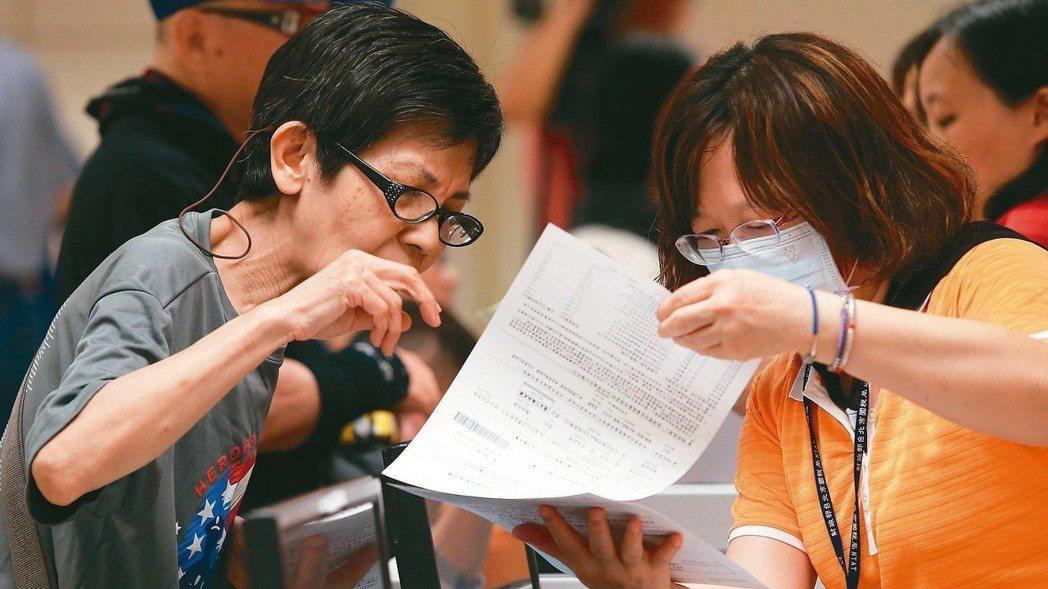 圖為台北市國稅局工作人員為民眾解說報稅程序。 報系資料照