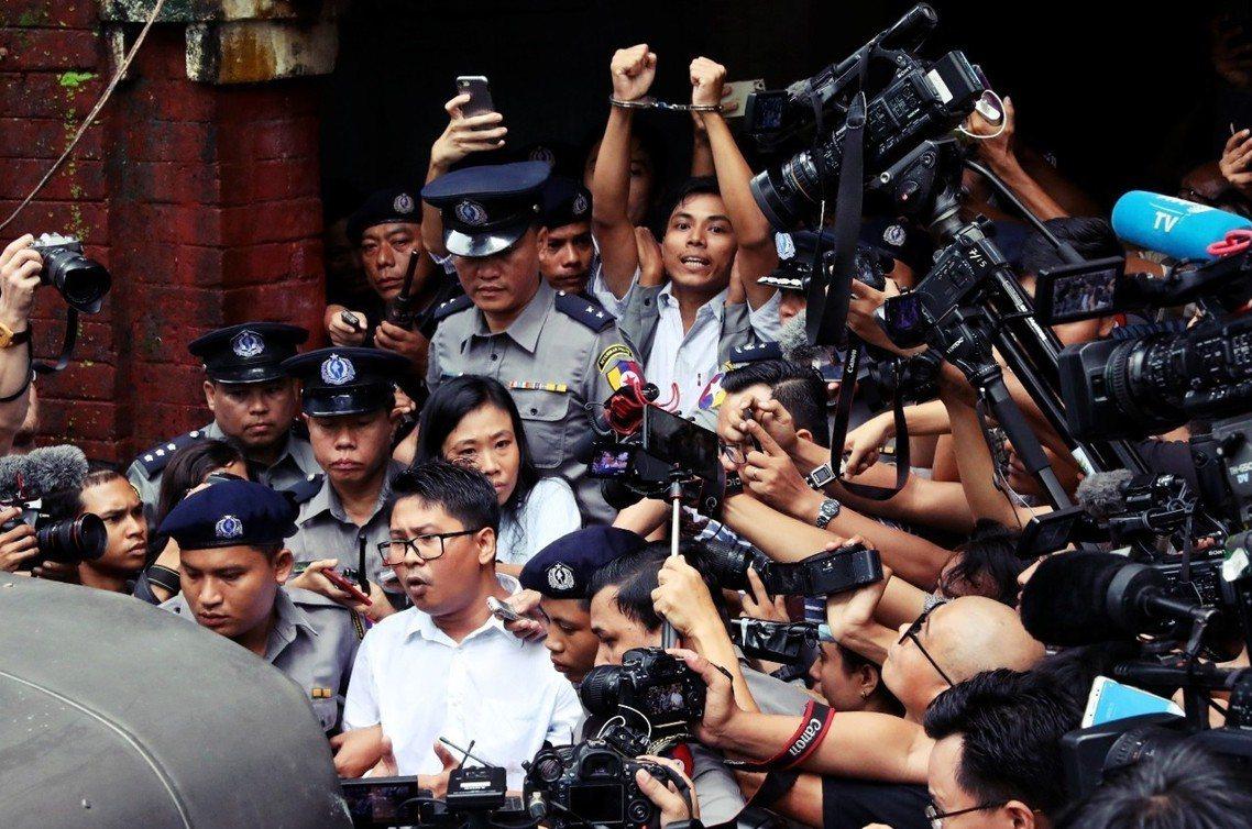 堅持清白的兩名緬甸記者瓦隆(白衣,前方進車者)和喬索歐(白衣,後方高舉手銬者)。...