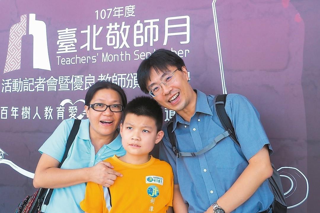劍潭國小林迺超老師(右)鼓勵張姓學童(中)寫作,一旁是學童的母親。 圖/北市教育...