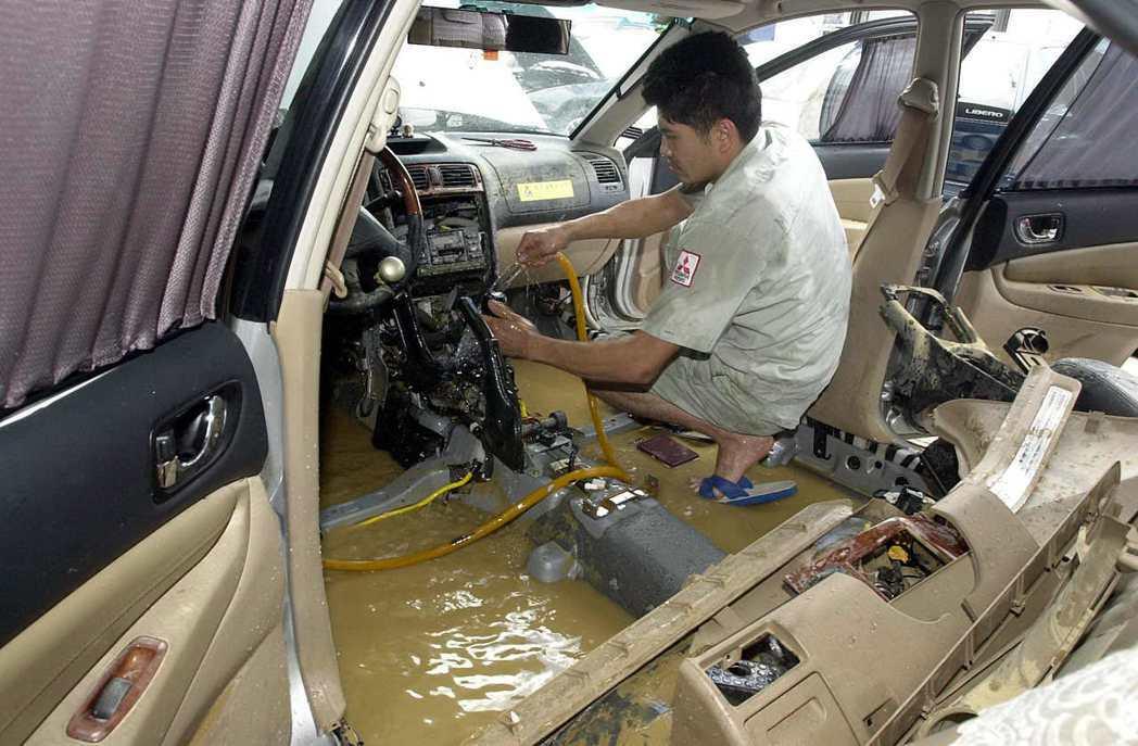 修車師傅拆解災情慘重的泡水車,逐一清洗滿是泥漿的零件。圖/聯合報系資料照片
