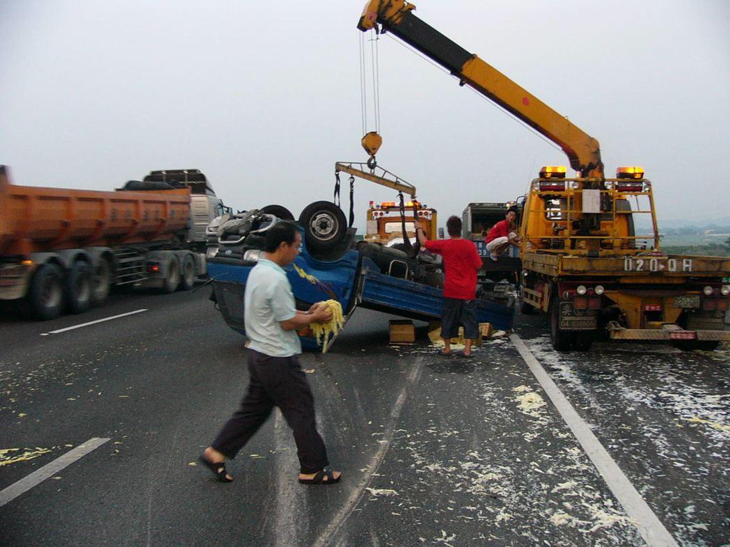 圖為滿載筍干的小貨車在高速公路翻車,筍干等散落一地,工作人員冒著危險清除路面上筍...