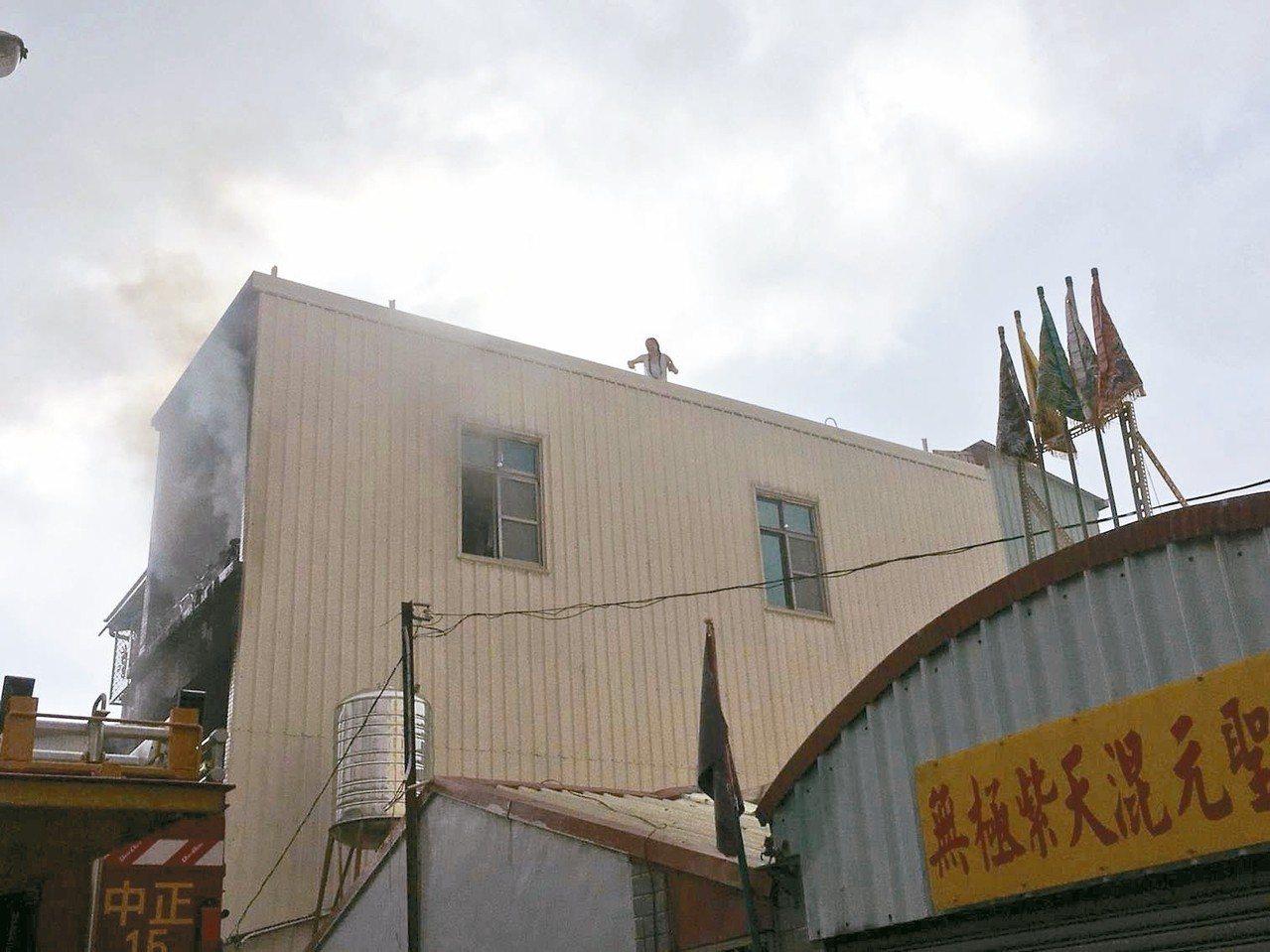 透天厝起火,董女爬上加蓋頂樓向消防員呼救,表示姊姊困在二樓未逃出。 圖/台南市消...