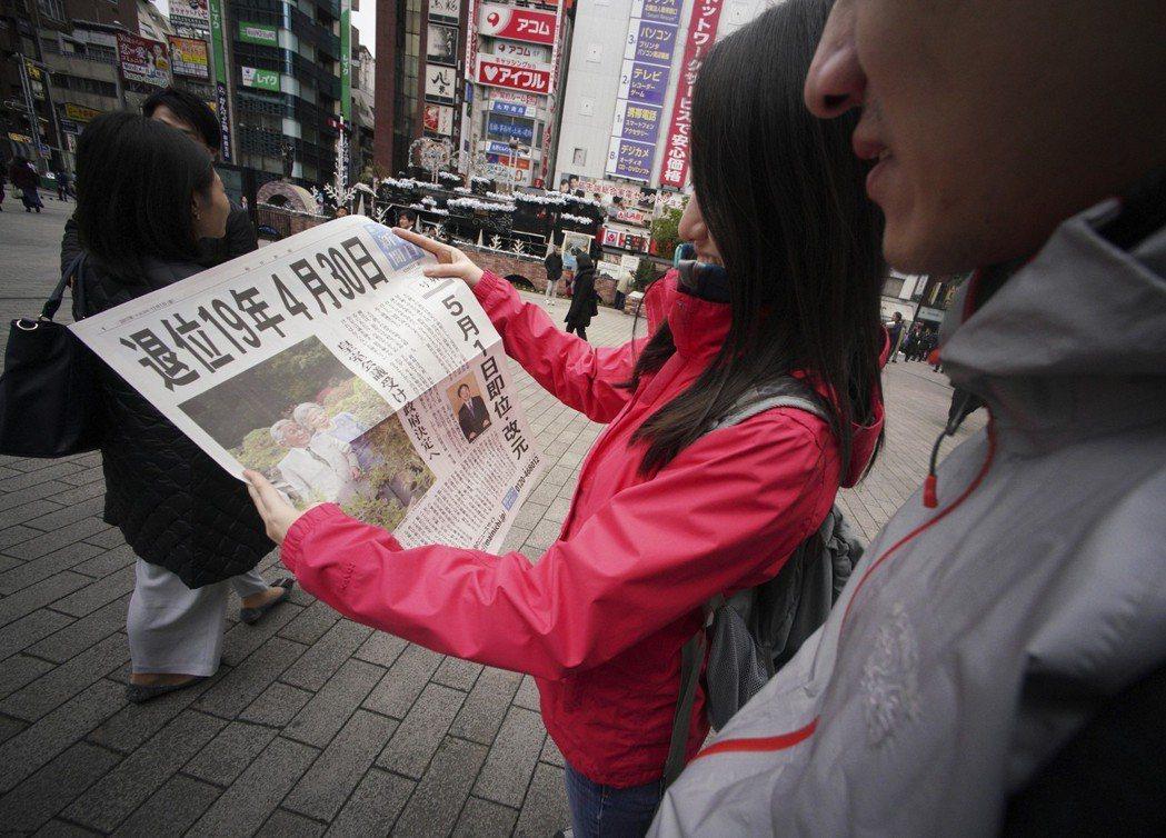 2017年12月1日,日皇明仁確定將在2019年退位,民眾在街頭閱讀報紙號外。(...