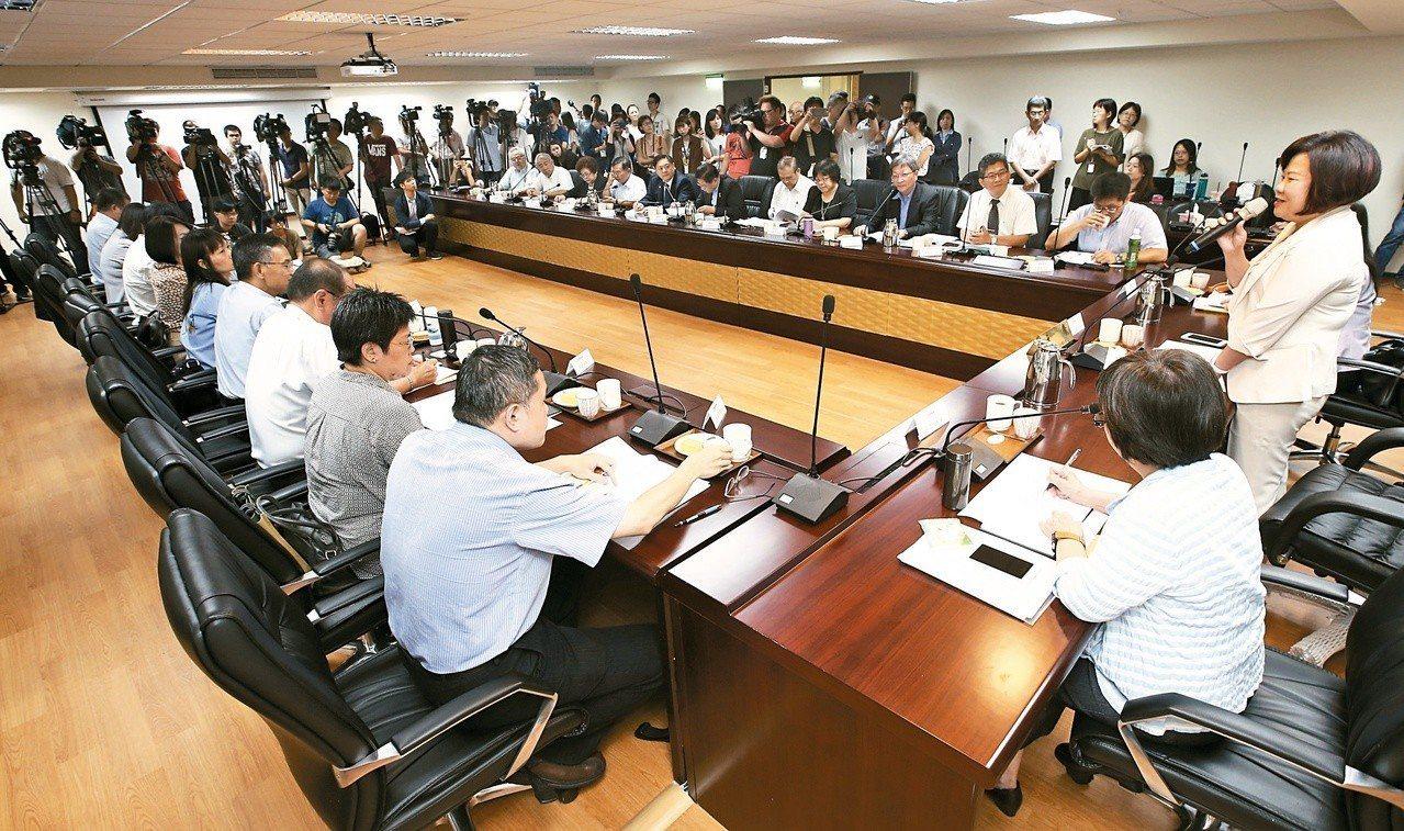 基本工資審議委員會八月舉行,由勞動部長許銘春(右一)主持,勞方和資方分別坐在會議...
