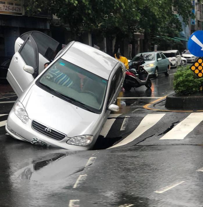 8月29日徐姓駕駛在高雄和平二路與一心路口停等紅燈時,突然道路塌陷,汽車卡在塌陷...