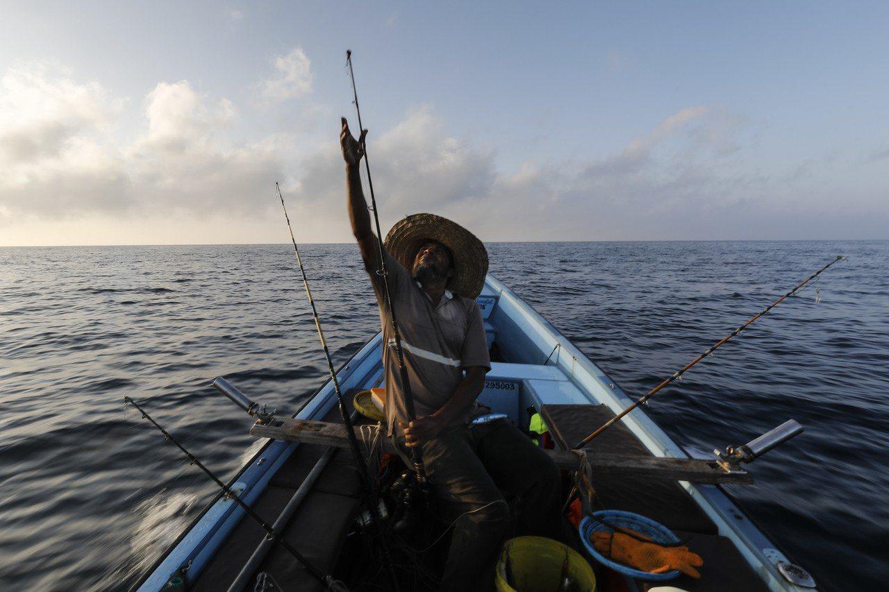 肯亞漁夫要幫手機穿保險套,以低花費達到防水效果。 歐新社資料照