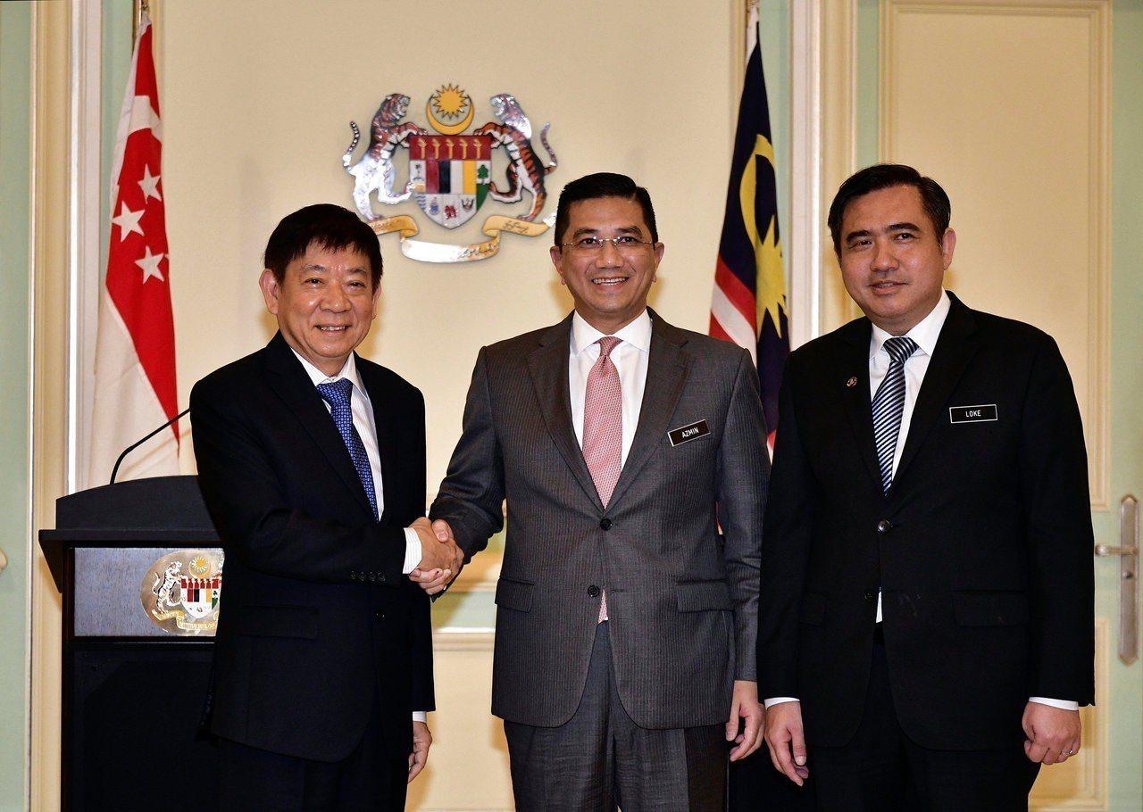 新加坡交通部長許文遠(左)5日與馬來西亞經濟部長阿茲敏(中)在記者會上握手,右為...