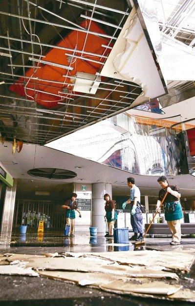 新千歲機場天花板因強震塌落,清潔人員忙著善後。 美聯社
