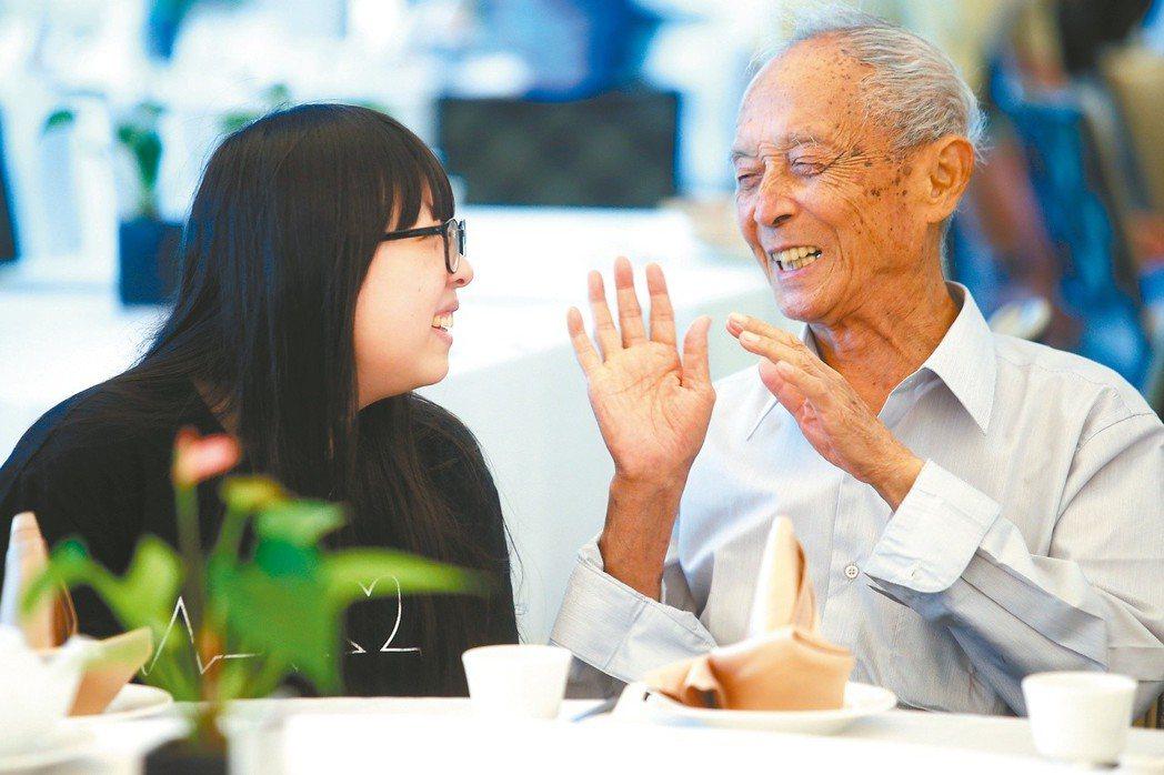 台北市陽明老人公寓七、八月慶生會,學生陳玟安(左)與張榮華爺爺話家常。 記者...
