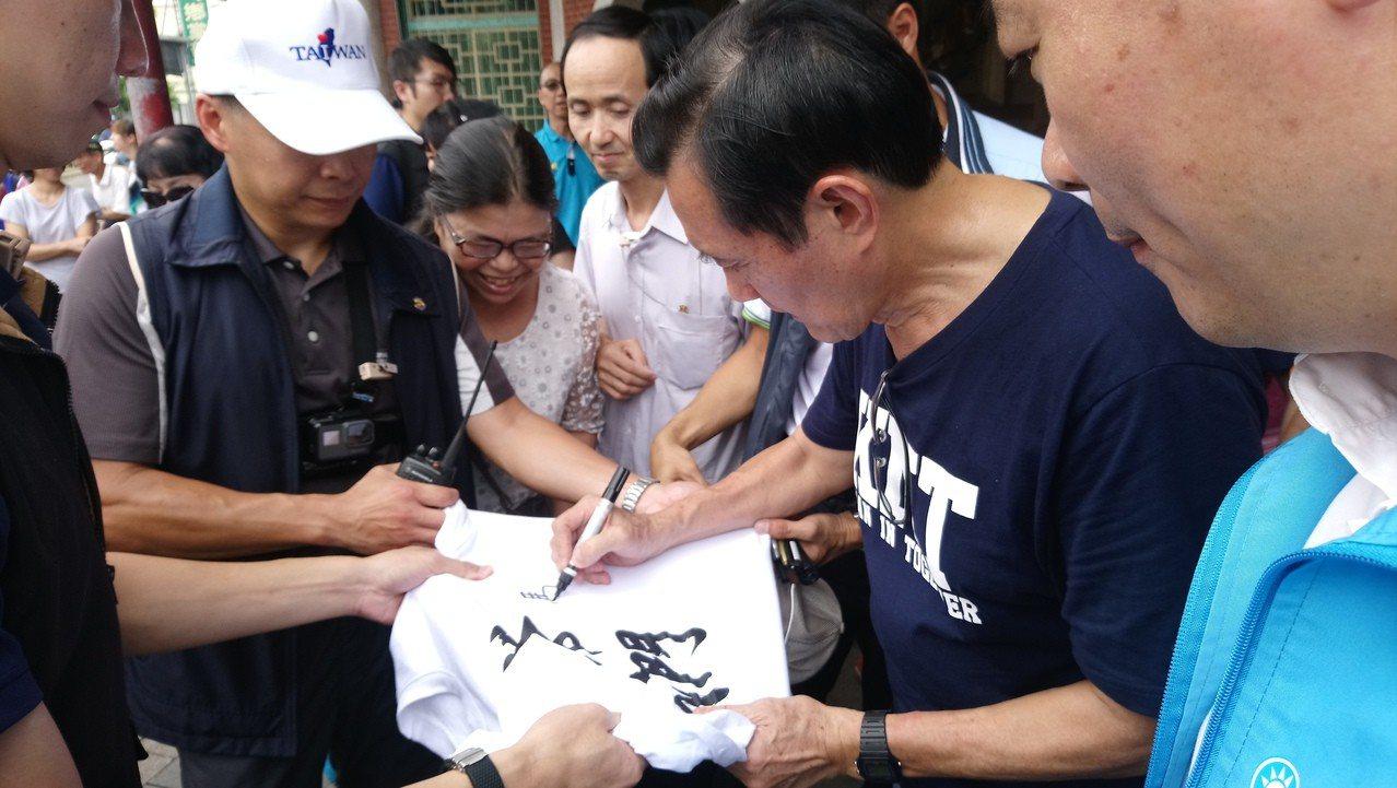 馬英九受邀在衣服上簽名。記者卜敏正/攝影
