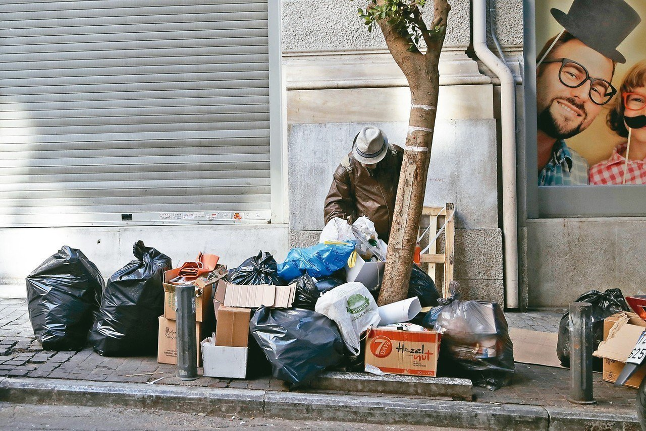 一名男子在雅典市中心翻著路邊的垃圾,想找到可用之物。 美聯社