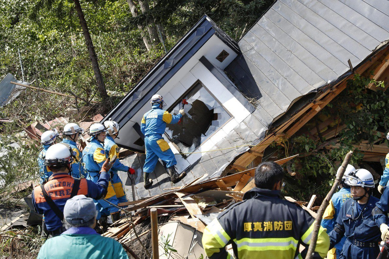 北海道厚真町接近震央,許多房屋倒塌,救難人員爬上一棟已傾倒的房屋,敲破二樓窗戶準...