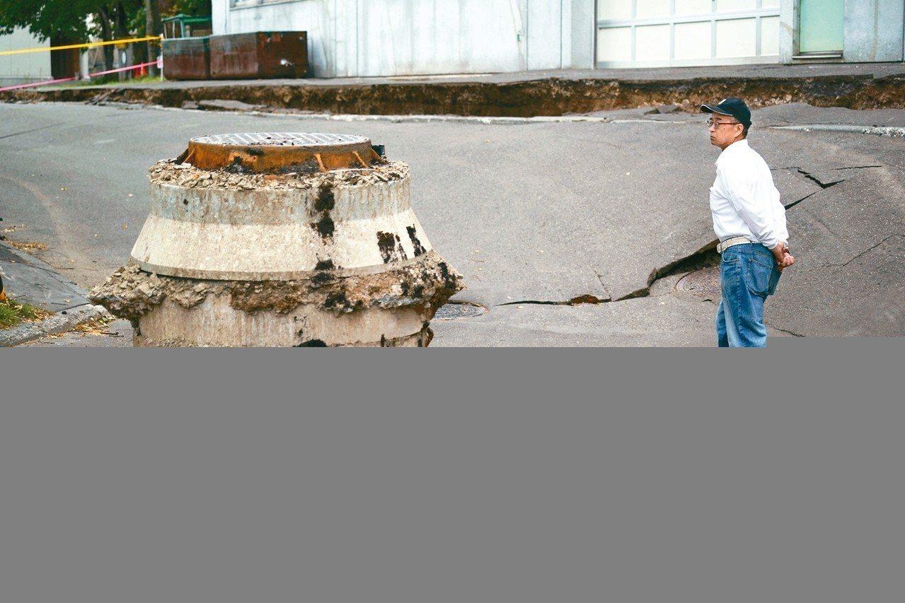 北海道6日清晨發生大地震,札幌郊外的清田區地面下陷又龜裂,一名當地居民從下陷處旁...