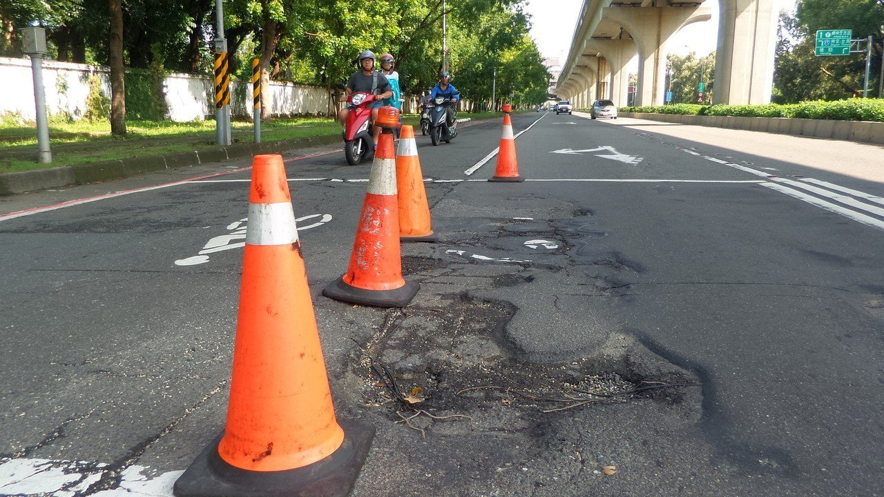 高雄市楠梓區左楠路中油宿舍前的道路破損,感應線圈也裸露。記者林保光/攝影