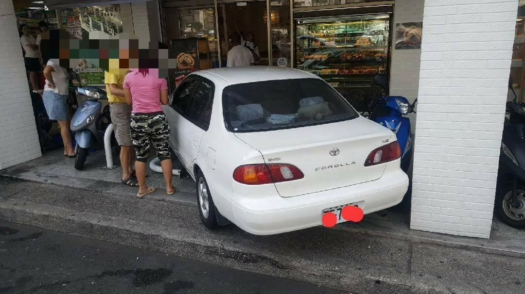 一名老阿伯誤踩油門,車衝騎樓,撞麵包店大門,嚇壞一堆人。記者游明煌/翻攝