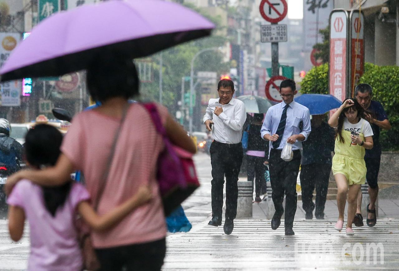 有民眾在雨中跑步過馬路躲雨。記者鄭清元/攝影