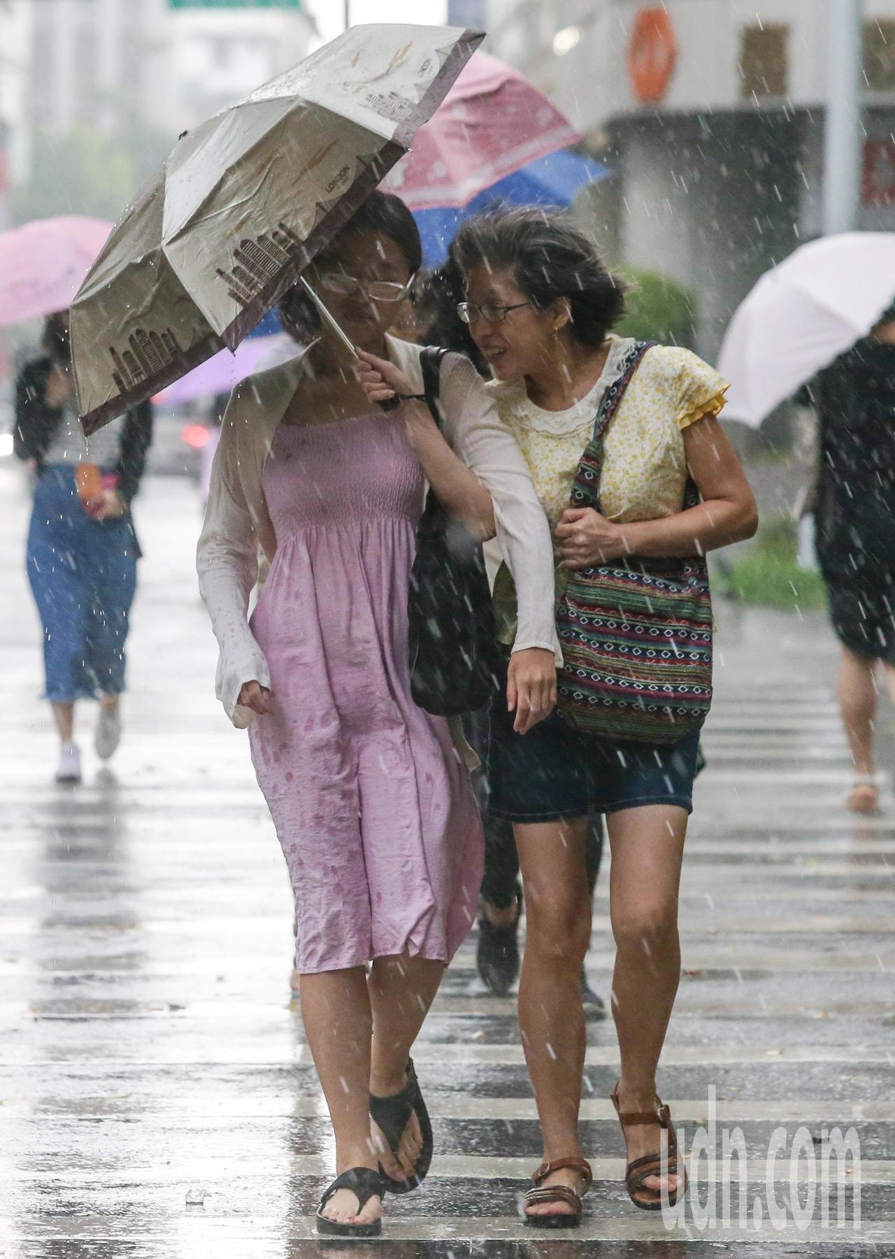 台北市今天下午突然出現豪大雨,民眾共撐一把傘擋雨。記者鄭清元/攝影
